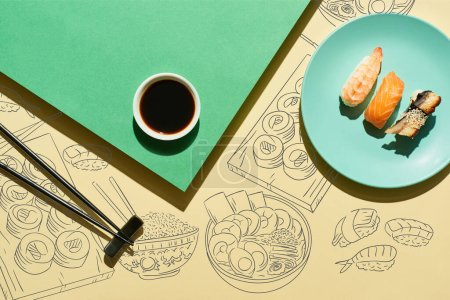 Photo for Top view of nigiri near soy sauce, chopsticks and japanese food illustration on green and yellow surface - Royalty Free Image