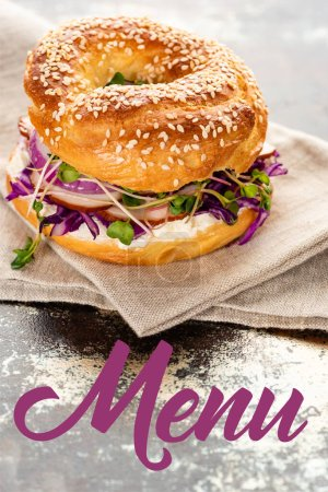 Photo for Fresh bagel on napkin near menu lettering on textured surface - Royalty Free Image