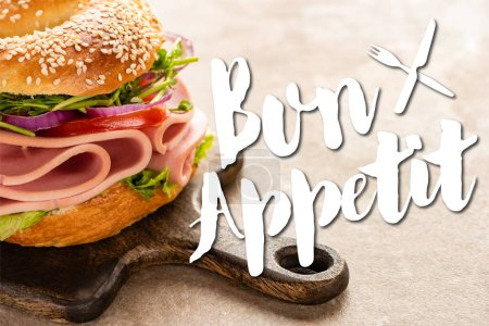Photo for Delicious bagel with ham on wooden cutting board near bon appetit lettering on textured surface - Royalty Free Image