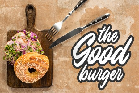 Photo for Top view of fresh bagel with meat on cutting board with cutlery near the good burger lettering on textured surface - Royalty Free Image