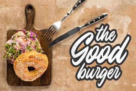 Photo pour Vue de dessus du bagel frais avec viande sur planche à découper avec couverts près du bon lettrage burger sur surface texturée - image libre de droit