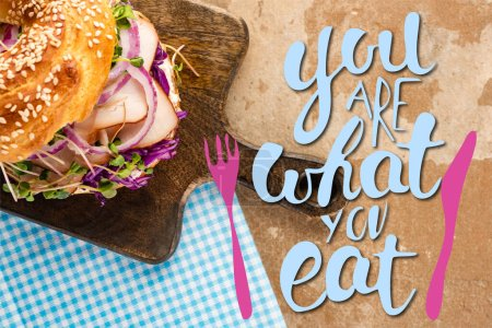 top view of fresh bagel with meat on cutting board and plaid napkin near you are what you eat lettering and cutlery illustration