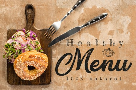 Photo for Top view of bagel with meat on cutting board with cutlery near the healthy menu lettering on textured surface - Royalty Free Image