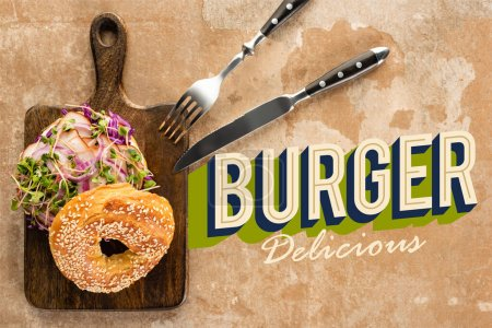 Photo for Top view of bagel with meat on cutting board with cutlery near burger delicious lettering on textured surface - Royalty Free Image