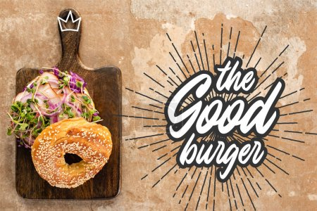 Photo for Top view of bagel with meat on cutting board with cutlery near the good burger lettering on textured surface - Royalty Free Image