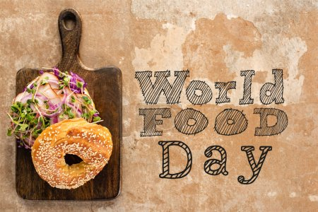 Photo for Top view of bagel with meat on cutting board with cutlery near world food day lettering on textured surface - Royalty Free Image