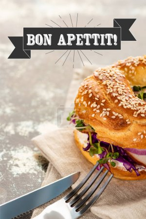 Photo for Fresh bagel with meat on napkin with cutlery near bon apettit lettering on textured surface - Royalty Free Image