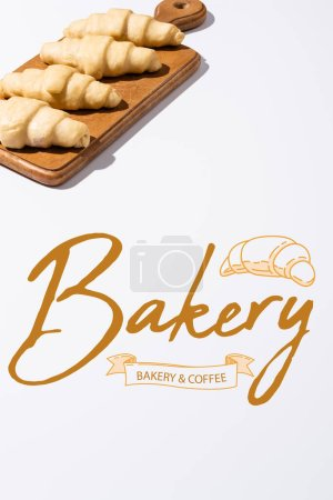 Photo for Raw croissants on wooden cutting board near bakery and coffee lettering on white background - Royalty Free Image