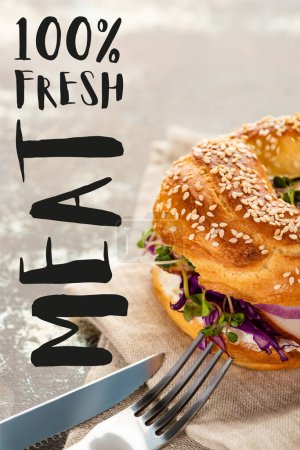 Photo for Tasty bagel with meat on napkin with cutlery near fresh meat lettering on textured surface - Royalty Free Image