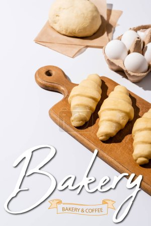 Photo for Raw croissants on wooden cutting board near eggs, dough, bakery and coffee lettering on white - Royalty Free Image