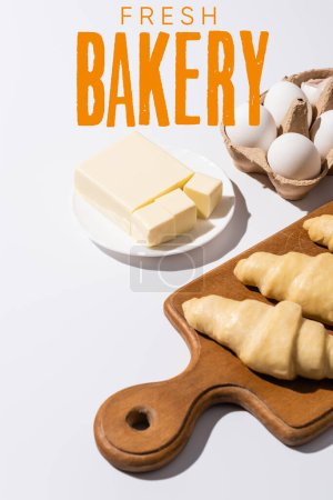 Photo for Raw croissants on wooden cutting board near butter, eggs and fresh bakery lettering on white background - Royalty Free Image