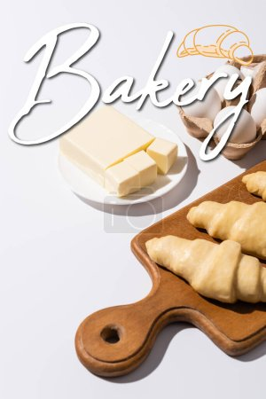 Photo for Raw croissants on wooden cutting board near butter, eggs and bakery lettering on white background - Royalty Free Image