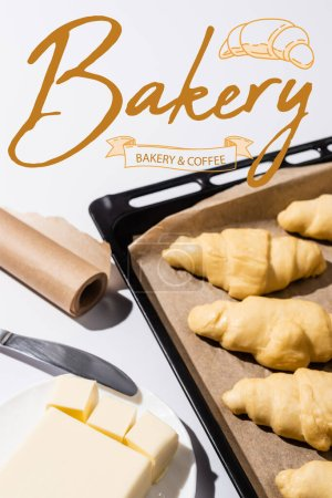 Photo for Selective focus of raw croissants on baking tray near butter, knife, bakery and coffee lettering on white - Royalty Free Image