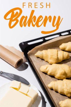 Photo pour Foyer sélectif de croissants crus sur plaque de cuisson, beurre, couteau près de la boulangerie fraîche lettrage sur blanc - image libre de droit