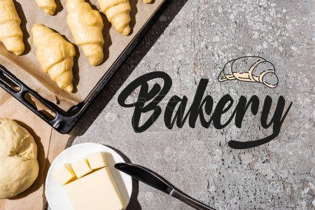 Photo for Top view of uncooked croissants on baking tray, dough and butter near bakery lettering on concrete grey surface - Royalty Free Image