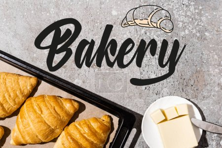Photo for Top view of baked croissants on baking tray near butter, knife and bakery lettering on concrete grey surface - Royalty Free Image