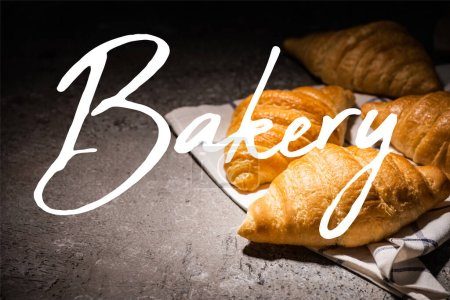 Photo for Fresh baked croissants on towel near bakery lettering on concrete grey surface - Royalty Free Image