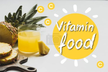 Photo for Fresh pineapple juice near sliced fruit on wooden cutting board near vitamin food lettering on white - Royalty Free Image