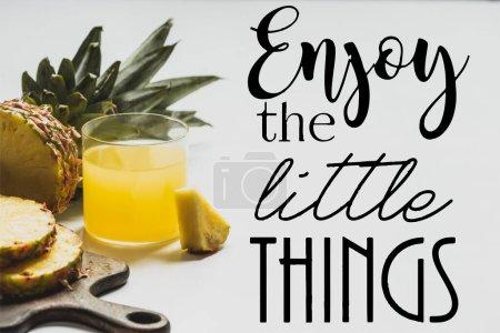 jugo de piña fresca cerca de la fruta en rodajas en la tabla de cortar de madera y disfrutar de las pequeñas cosas que escriben en blanco