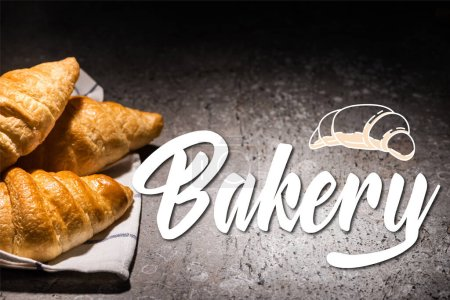 Photo for Fresh baked croissants on towel near bakery lettering and illustration on concrete grey surface - Royalty Free Image
