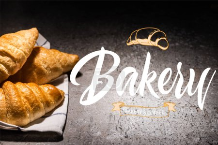 Photo for Fresh croissants on towel near bakery and coffee lettering on concrete grey surface - Royalty Free Image