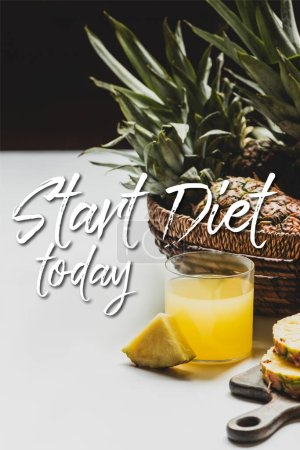 Photo for Fresh pineapple juice near delicious fruit on wooden cutting board and start diet today lettering on white and black - Royalty Free Image