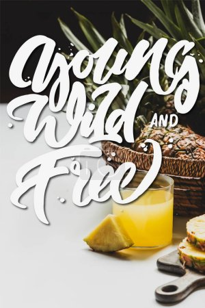Photo for Fresh pineapple juice near delicious fruit on wooden cutting board and young, wild and free lettering on white and black - Royalty Free Image