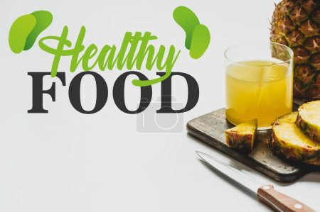 Photo for Pineapple juice in glass near delicious fruit on cutting board and healthy food lettering on white - Royalty Free Image