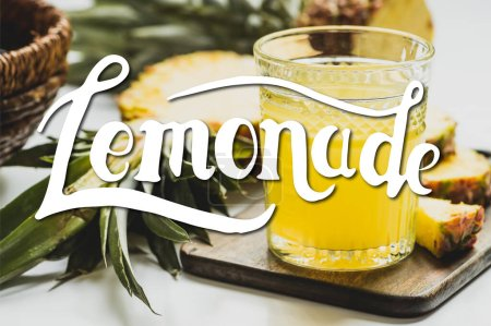 Photo for Selective focus of fresh pineapple juice in glass near delicious fruit on cutting board and lemonade lettering on white - Royalty Free Image