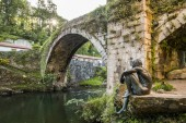 Lierganes, Spain. The Puente Viejo (Old Bridge), with the statue of the Hombre Pez (Fish-man), an entity which belongs to the mythology of Cantabria, named Francisco de la Vega Casar