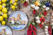 Hand painted plate with the Castello Scaligero in Sirmione, Italy, hanging on a wall with a set of pottery made fruits and vegetables