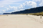 People walking in Benone Strand and Downhill Beach, a large sand strand in Castlerock, Derry County, Northern Ireland