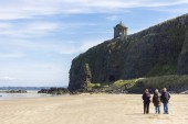 People walking in Downhill Beach, with the iconic Mussenden Temple on top of the cliffs. Castlerock, Derry County, Northern Ireland