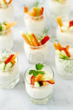 Snack in a glass with fresh cream and various vegetables on a light background. Selective focus.