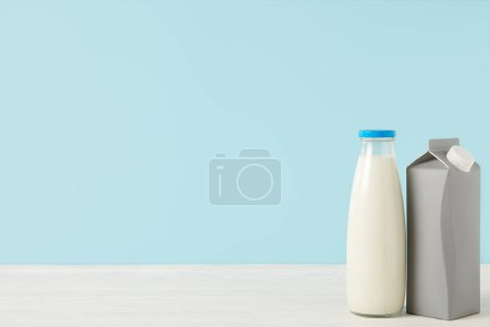 closeup image of milk in bottle and blank carton package on blue background