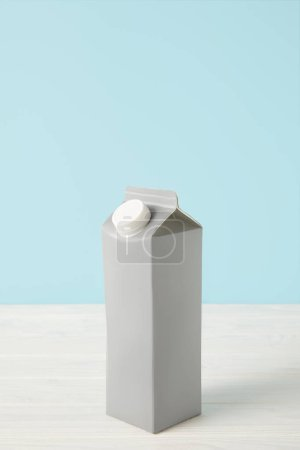 milk in blank carton package on blue background