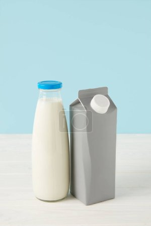 milk in bottle and blank carton package on blue background