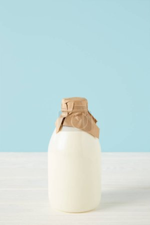closeup view of fresh milk in bottle wrapped by paper on blue background