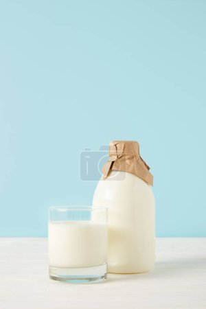 closeup shot of milk glass and milk in bottle wrapped by paper on blue background