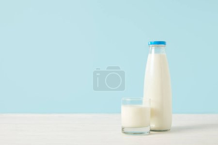 closeup image of milk bottle and milk glass on blue background