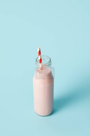 closeup view of strawberry milkshake in bottle with drinking straw on blue background