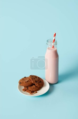 Photo for Chocolate cookies in saucer and strawberry milkshake in bottle with drinking straw on blue background - Royalty Free Image
