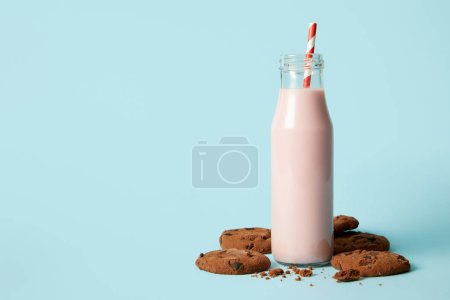 chocolate cookies and milkshake in bottle with drinking straw on blue background