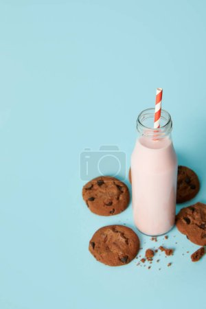 closeup view of chocolate cookies and milkshake in bottle with drinking straw on blue background