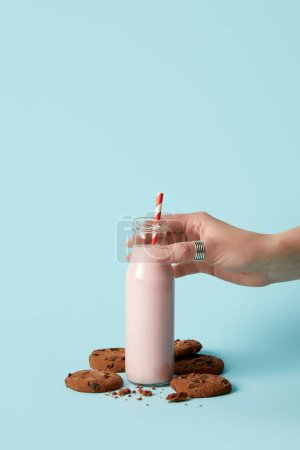 cropped image of woman holding bottle with strawberry milkshake and chocolate cookies on blue background