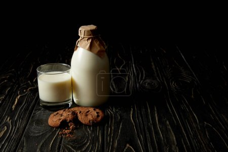 chocolate cookies, fresh milk in glass and bottle wrapped by paper on black background