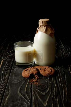 close up view of chocolate cookies, fresh milk in glass and bottle wrapped by paper on black background