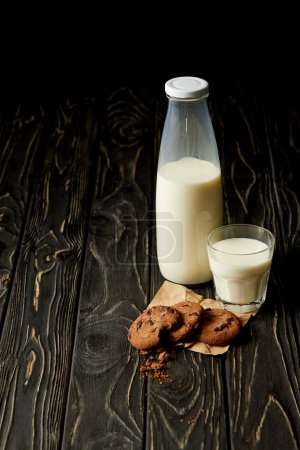 closeup view of chocolate cookies, milk in bottle and glass on wooden background