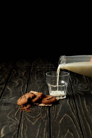 cropped image of person pouring milk into glass from bottle and chocolate cookies on black wooden surface