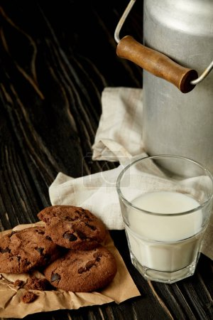 chocolate cookies, milk in glass and aluminium can on sackcloth